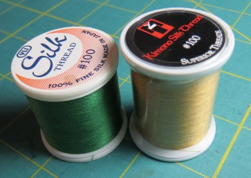 YLI and Superior make size 100 silk threads, good for applique and machine quilting